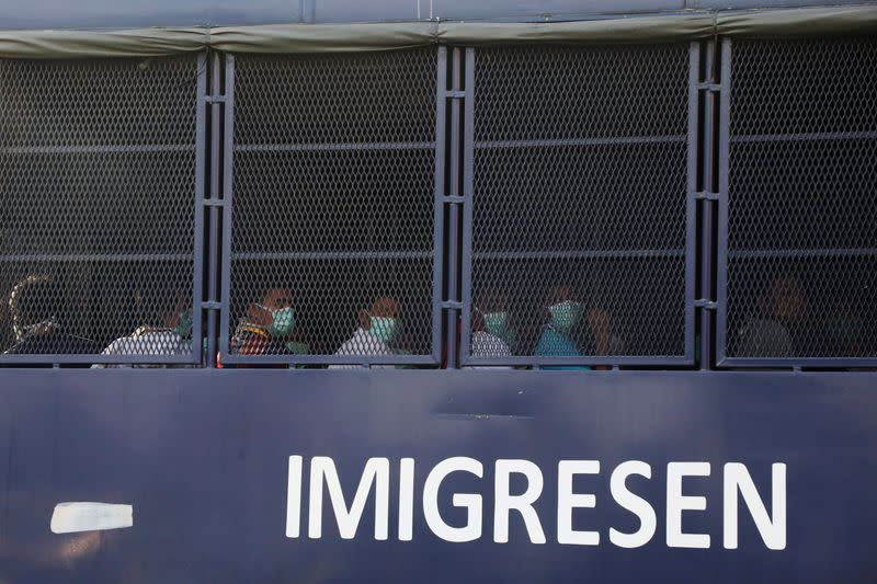 FILE PHOTO: Myanmar migrants to be deported from Malaysia are seen inside an immigration truck, in Lumut