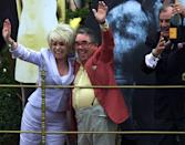 East Enders star Barbara Windsor (L) joins comedian Ronnie Corbett in saluting the Queen from a parade float during Golden Jubilee celebrations June 4, 2002. REUTERS/Chris Helgren CLH/