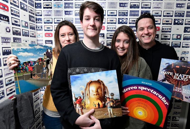 From left, Shay Toland and her two teenagers, 15-year-old Maeve and 17-year-old Aidan, and Husband Brian, with albums in front of tape cassette wallpaper at their home, examples of how so many old-school items - records, Dungeons and Dragons, etc - are back in vogue.