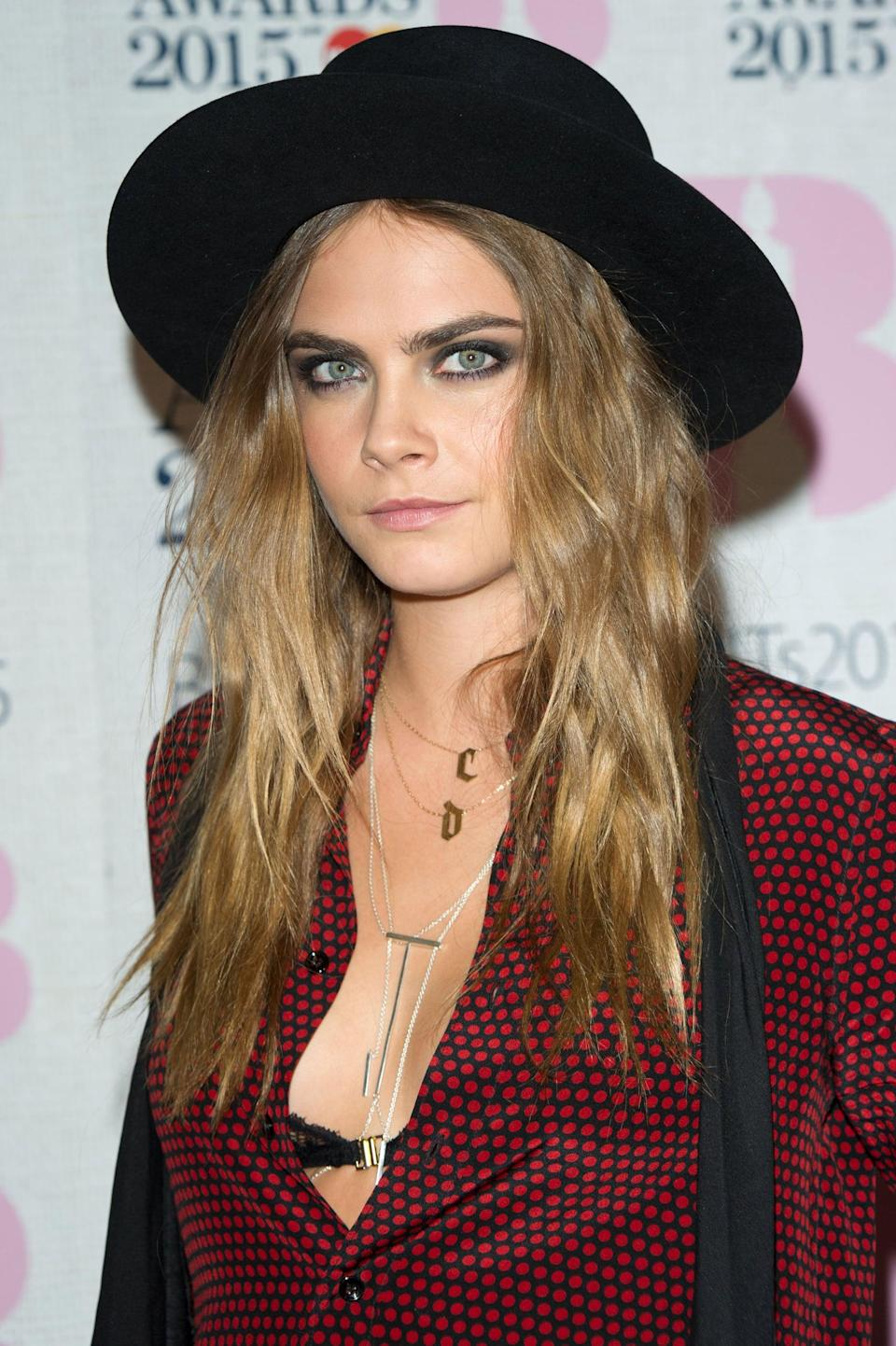 <p>Delevingne fully embraced the model-off-duty aesthetic with matte, purposefully-dishevelled waves, heavy black eye liner, and another superstylish black hat. </p>