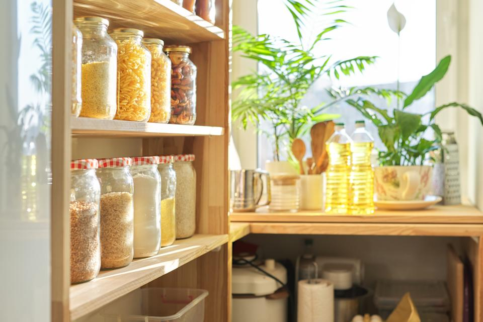 Food storage at home, sunflower oil on table in pantry. Pantry interior, wooden shelf with food cans and kitchen utensils