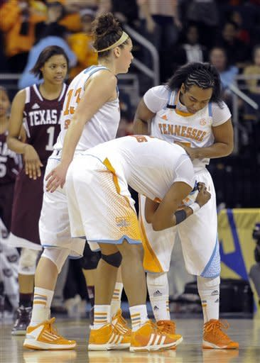 Tennessee guard Kamiko Williams covers her head as guard Ariel Massengale, right, consoles her and guard/forward Taber Spani (13) walks by in the closing moments of an NCAA college basketball game against Texas A&M in the Southeastern Conference tournament, Saturday, March 9, 2013, in Duluth, Ga. Texas A&M won 66-62. (AP Photo/John Amis)