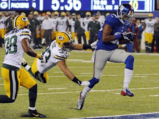 New York Giants wide receiver Rueben Randle breaks away from Green Bay Packers cornerback Micah Hyde (33) and Tramon Williams (38) for a touchdown during the first half of an NFL football game Sunday, Nov. 17, 2013, in East Rutherford, N.J. (AP Photo/Bill Kostroun)