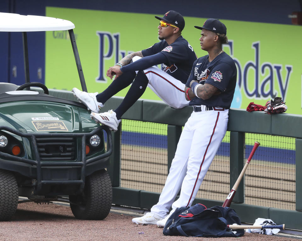 Atlanta Braves infielder Johan Camargo, left, and outfielder Cristian Pache watch spring training baseball practice in North Port, Fla., Wednesday, Feb. 24, 2021. (Curtis Compton/Atlanta Journal-Constitution via AP)