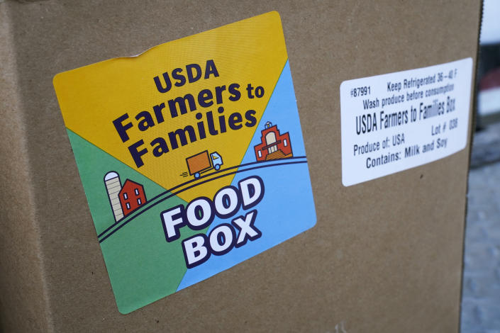 A USDA Farmers to Families Food Box is seen at a Des Moines Area Religious Council mobile food pantry stop at the downtown bus station, Thursday, Feb. 18, 2021, in Des Moines, Iowa. Agricultural groups and anti-hunger organizations are pushing the Biden administration to continue the Farmers to Families Food Box program launched by President Donald Trump that spent $6 billion to prevent farmers from plowing under food and instead provide it to millions of Americans left reeling by the coronavirus pandemic. (AP Photo/Charlie Neibergall)