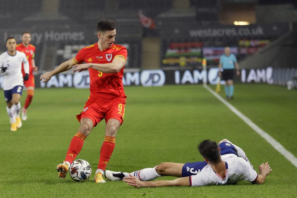 United States' Matt Miazga falls as Wales' Tom Lawrence keeps the ball during the international friendly soccer match between Wales and USA at Liberty stadium in Swansea, Wales, Thursday, Nov. 12, 2020. (AP Photo/Kirsty Wigglesworth)