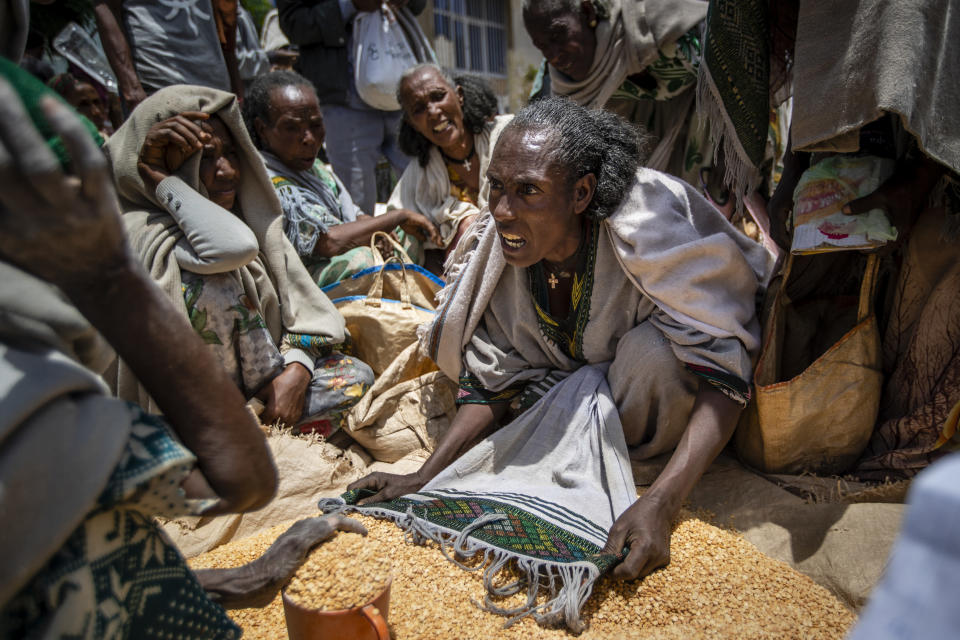 """FILE - In this Saturday, May 8, 2021 file photo, an Ethiopian woman argues with others over the allocation of yellow split peas after it was distributed by the Relief Society of Tigray in the town of Agula, in the Tigray region of northern Ethiopia. In an interview with The Associated Press Tuesday, Sept 28, 2021, the United Nations humanitarian chief Martin Griffiths calls the crisis in Ethiopia a """"stain on our conscience"""" as children and others starve to death in the Tigray region under what the U.N. calls a de facto government blockade of food, medical supplies and fuel. (AP Photo/Ben Curtis, File)"""