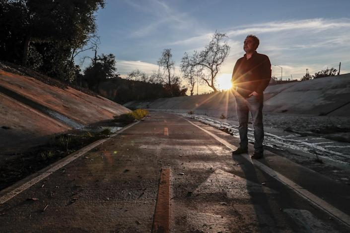 Rodney Ascher stands next to a road and trees while the sun shines between trees behind him.
