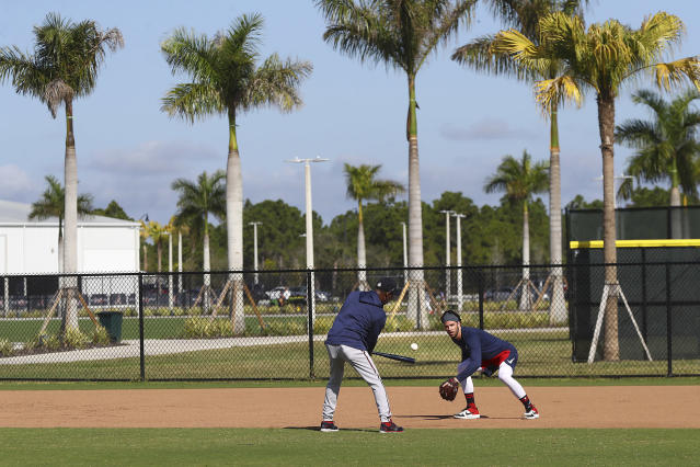 Atlanta Braves shortstop Dansby Swanson, right, takes ground balls from third base coach Ron Washington as position players reported to baseball spring training Monday, Feb. 17, 2020, in North Port, Fla. (Curtis Compton/Atlanta Journal-Constitution via AP)