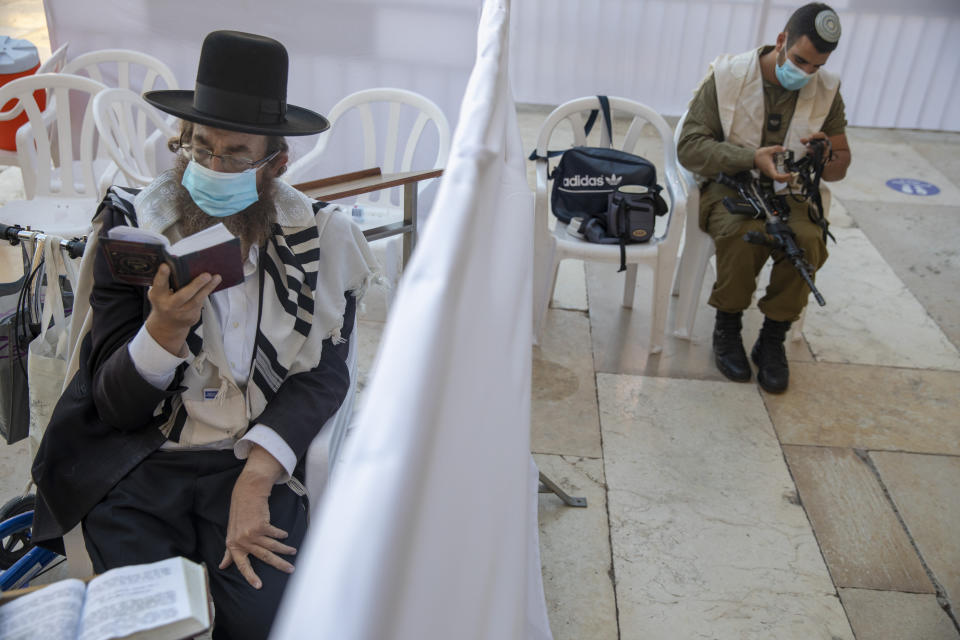 With social distancing barrier, an ultra-Orthodox Jewish man and an Israeli soldier pray ahead of Yom Kippur, the holiest day in the Jewish year which starts at sundown Sunday during a three-week nationwide lockdown to curb the spread of the coronavirus at the Western Wall, the holiest site where Jews can pray in Jerusalem's old city, Sunday, Sept. 27, 2020. The solemn Jewish holiday of Yom Kippur, which annually sees Israeli life grind to a halt, arrived on Sunday in a nation already under a sweeping coronavirus lockdown. (AP Photo/Ariel Schalit)