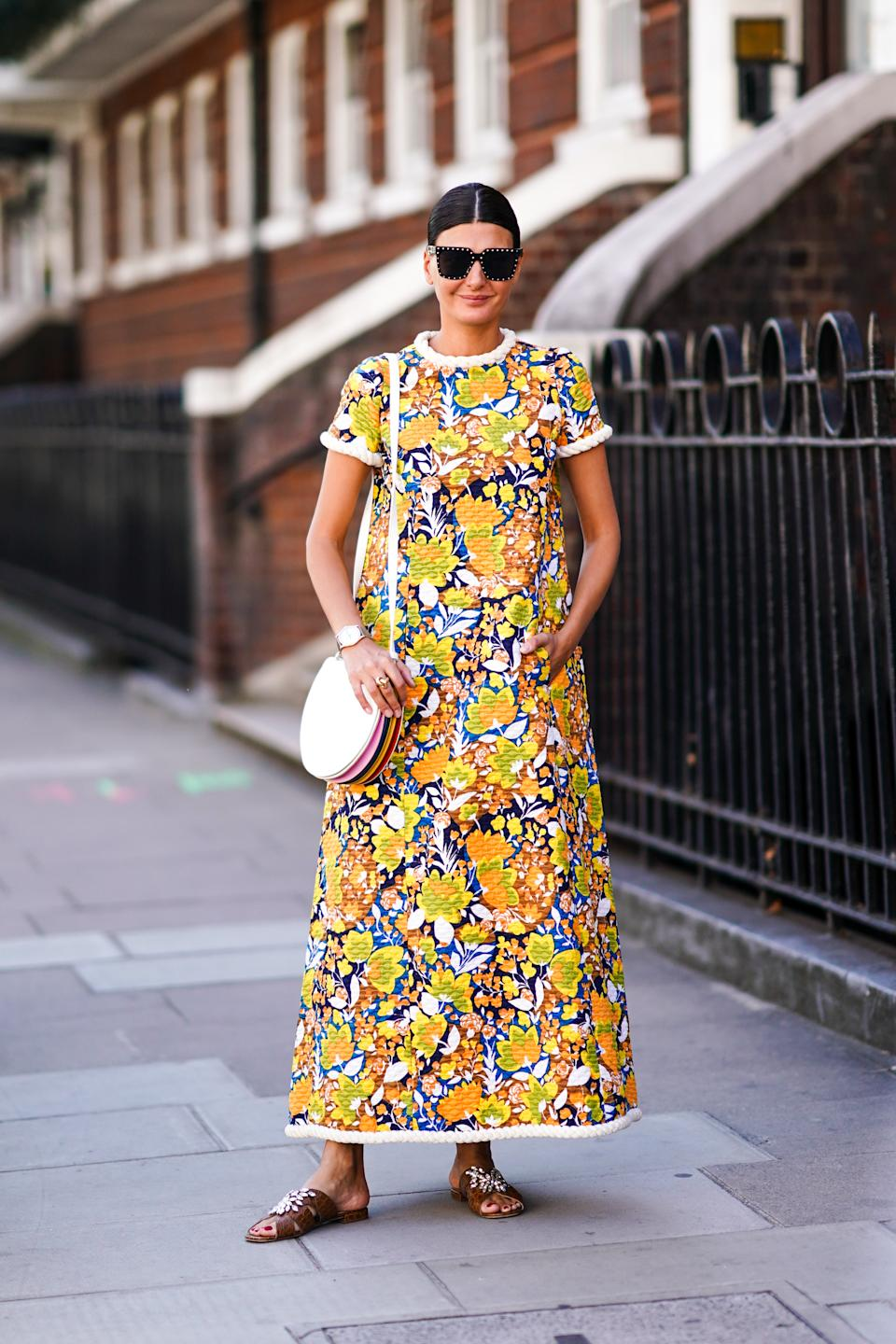 Giovanna Battaglia is seen wearing a coloured floral print dress, sunglasses, a bag, brown sandals. [Photo: Getty Images]