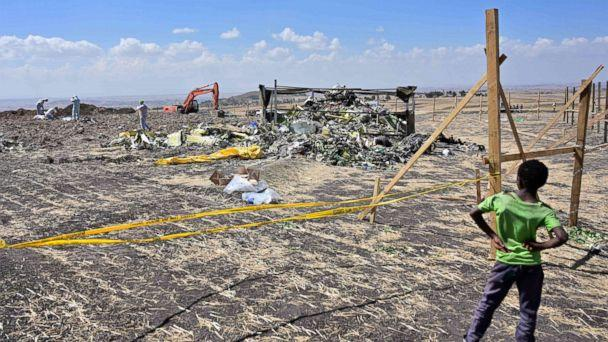 PHOTO: A boy look as forensic investigators comb the ground for DNA evidence near a pile of twisted airplane debris at the crash site of an Ethiopian airways operated Boeing 737 MAX aircraft, March 16, 2019, near Bishoftu in Ethiopia. (Tony Karumba/AFP/Getty Images)