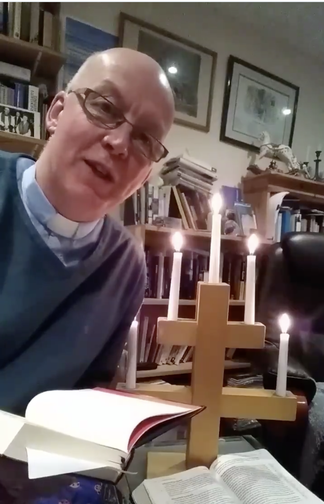 Stephen Beach reading from his sermon book beside candles