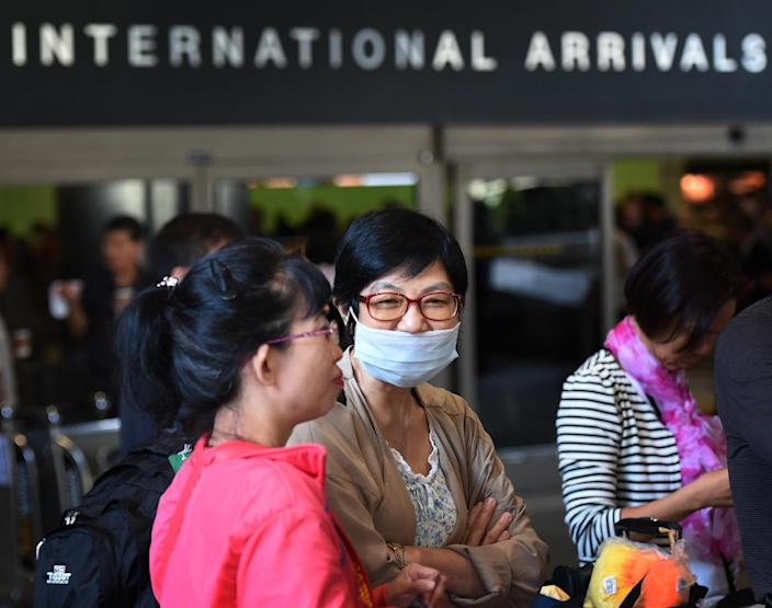A passenger arrives wearing a face mask at Los Angeles International Airport amid fears of Ebola (AFP Photo/Mark Ralston)