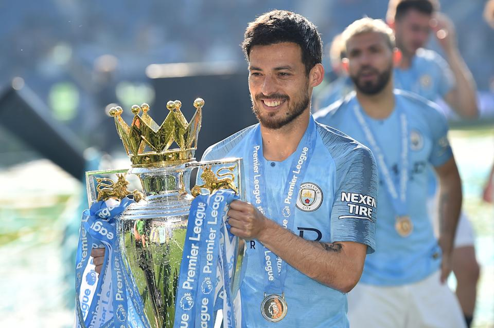 Manchester City's Spanish midfielder David Silva poses with the Premier League trophy after their 4-1 victory in the English Premier League football match between Brighton and Hove Albion and Manchester City at the American Express Community Stadium in Brighton, southern England on May 12, 2019. - Manchester City held off a titanic challenge from Liverpool to become the first side in a decade to retain the Premier League on Sunday by coming from behind to beat Brighton 4-1 on Sunday. (Photo by Glyn KIRK / AFP) / RESTRICTED TO EDITORIAL USE. No use with unauthorized audio, video, data, fixture lists, club/league logos or 'live' services. Online in-match use limited to 120 images. An additional 40 images may be used in extra time. No video emulation. Social media in-match use limited to 120 images. An additional 40 images may be used in extra time. No use in betting publications, games or single club/league/player publications. /         (Photo credit should read GLYN KIRK/AFP/Getty Images)