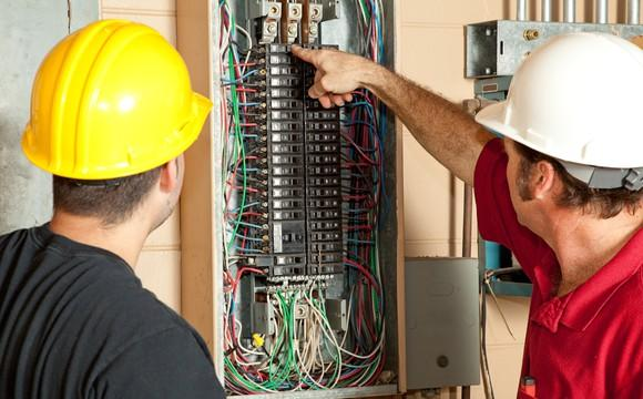 Two electricians replacing a circuit breaker