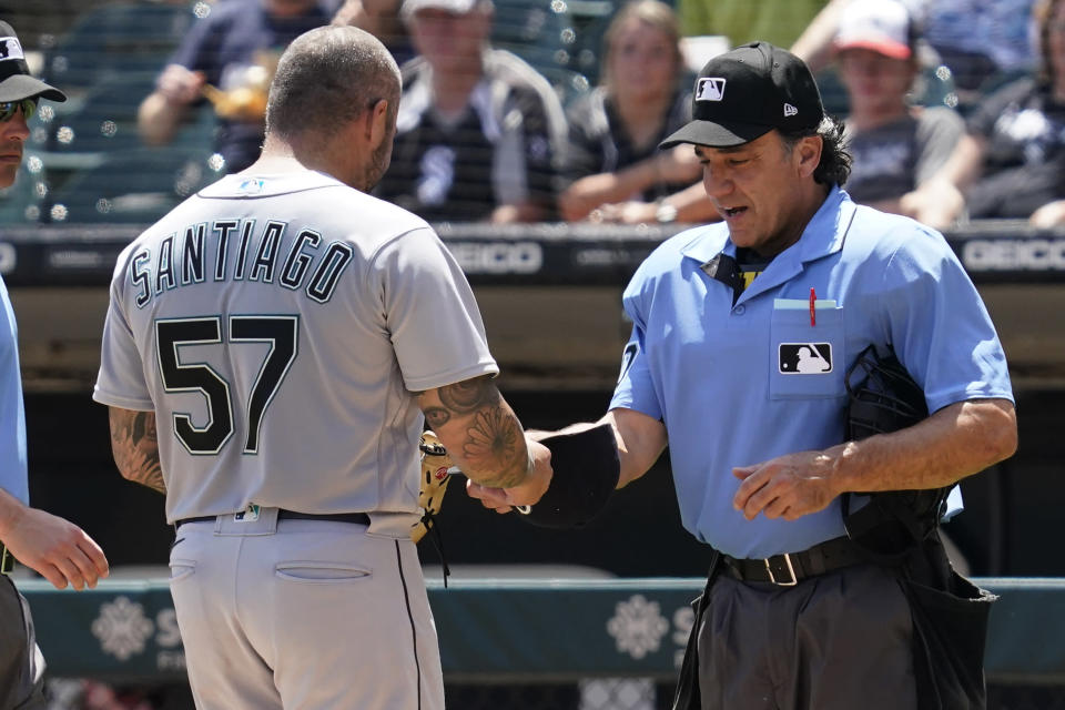 Home Plate umpire Phil Cuzzi, right, talks with Seattle Mariners relief pitcher Hector Santiago during the fifth inning in the first baseball game of a doubleheader against the Chicago White Sox in Chicago, Sunday, June 27, 2021. Santiago was ejected by Cuzzi. (AP Photo/Nam Y. Huh)