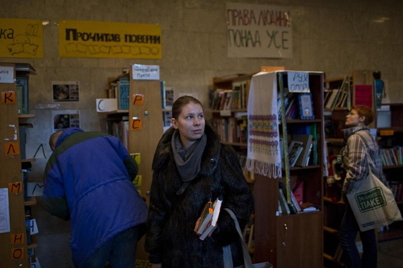 In this photo taken on Thursday, Feb. 6, 2014, Ukrainian protesters choose books organized on shelves in an improvised library set inside the Ukrainian House in Kiev. When the fervor flags for the protesters in Ukraine's capital and they want to get away from the barricades for a little while, many of them are heading to an improvised library in one of the buildings seized by demonstrators. (AP Photo/Emilio Morenatti)