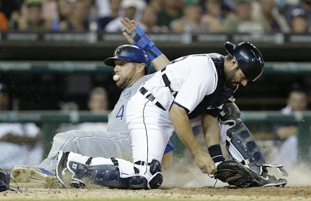 Kansas City Royals' Alex Gordon slides safely into home plate as Detroit Tigers catcher Alex Avila can't handle the throw on a error by pitcher Evan Reed in the seventh inning of a baseball game in Detroit, Monday, June 16, 2014. Mike Moustakas was safe at first base on the throwing error at home plate. (AP Photo/Paul Sancya)