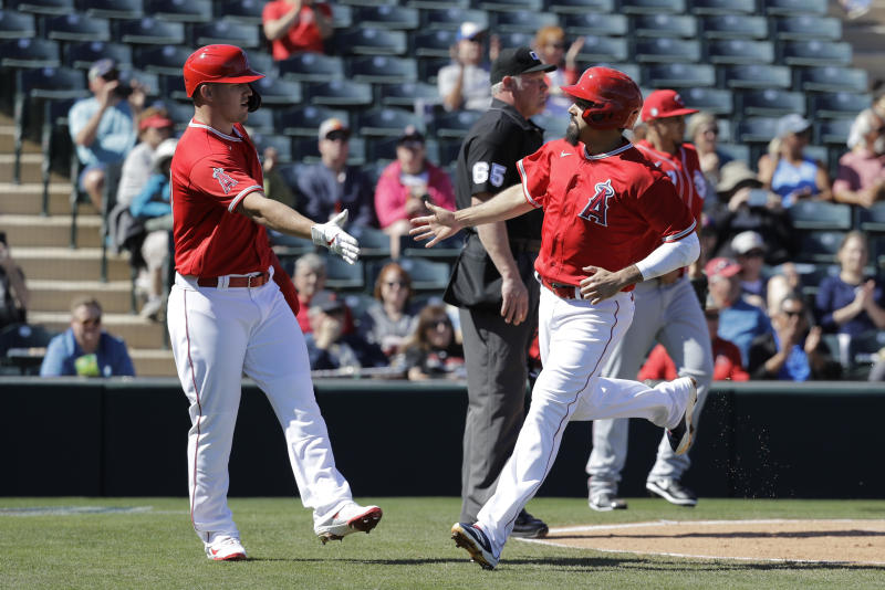 Los Angeles Angels' Mike Trout, left, and Anthony Rendon react after scoring during the first inning of a spring training baseball game against the Cincinnati Reds, Tuesday, Feb. 25, 2020, in Tempe, Ariz. (AP Photo/Darron Cummings)