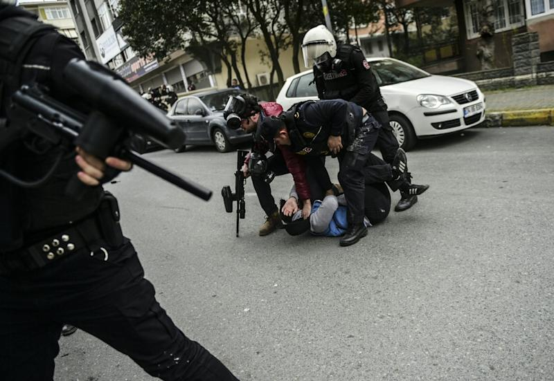Police officers detain a Kurdish man while people run away as Turkish riot policemen use rubber bullet to prevent people from gathering for a Nevruz celebration in Istanbul on March 20, 2016