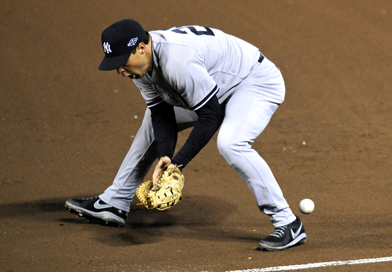 A ground ball that was hit by Baltimore Orioles' Nate McLouth bounces past New York Yankees first baseman Mark Teixeira in the fifth inning of Game 2 of the American League division baseball series on Monday, Oct. 8, 2012, in Baltimore. McLouth reached first base on Texeira's error. (AP Photo/Nick Wass)