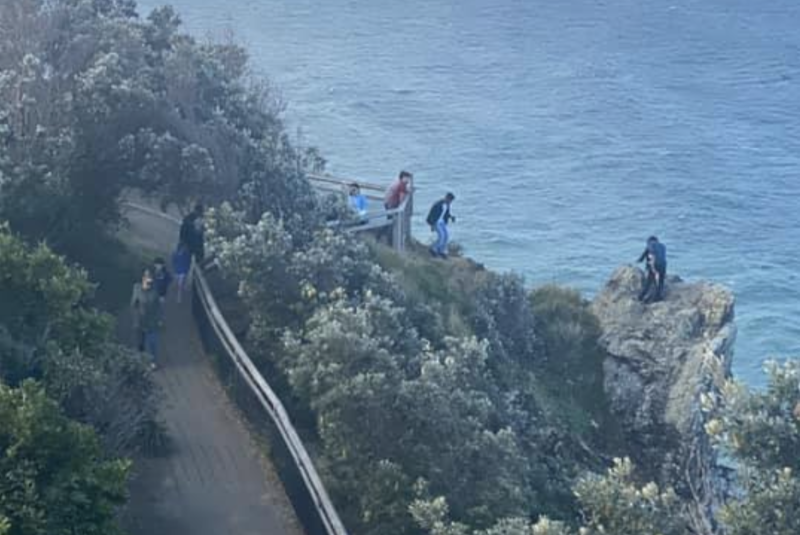 Pictured is a person standing on a cliff near Cape Byron Lighthouse while two others close by watch on.