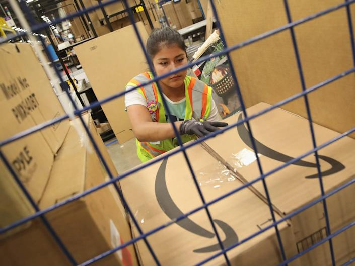 A worker packs a customer order at the 750,000-square-foot Amazon fulfillment center in Romeoville, Illinois.