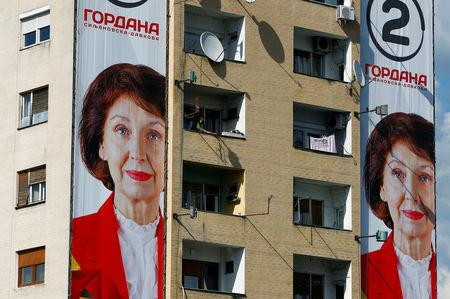 A woman cleans her balcony next to an election campaign poster of the opposition presidential candidate Gordana Dafkova-Siljanovska for presidential election on April 21 in Skopje, North Macedonia April 19, 2019. REUTERS/Ognen Teofilovski
