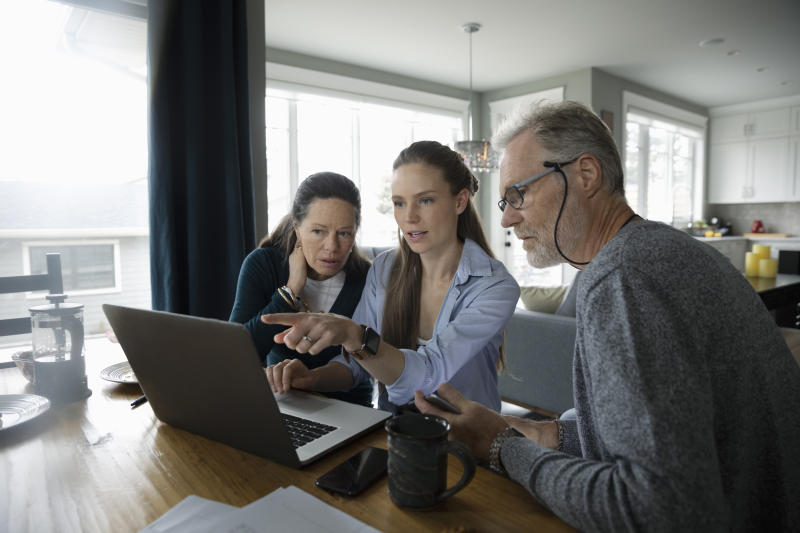 Parents and adult daughter using laptop at dining table