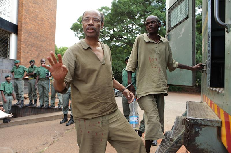 Former US Congressman Mel Reynolds, centre left, prepares to enter a prison truck while handcuffed following his court appearance at the magistrates courts in Harare, Thursday, Feb. 20, 2014. Reynolds was arrested in Zimbabwe for allegedly possessing pornographic material and violating immigration laws. (AP Photo/Tsvangirayi Mukwazhi)