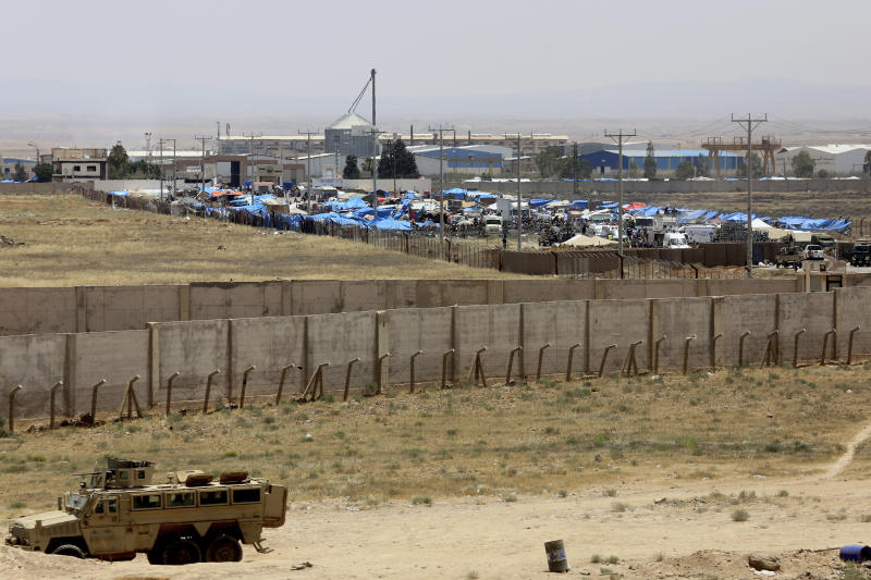 Delivery operations to displaced Syrians who gathered at a former free trade zone in northeast Jordan near Jabir crossing, Tuesday, July 3, 2018. The UN says Syria government's Russian-backed offensive to recover southern territories from rebels has displaced 270,000 people, 60,000 of them headed near the sealed Jordanian borders.(AP Photo/Raad Adayleh)