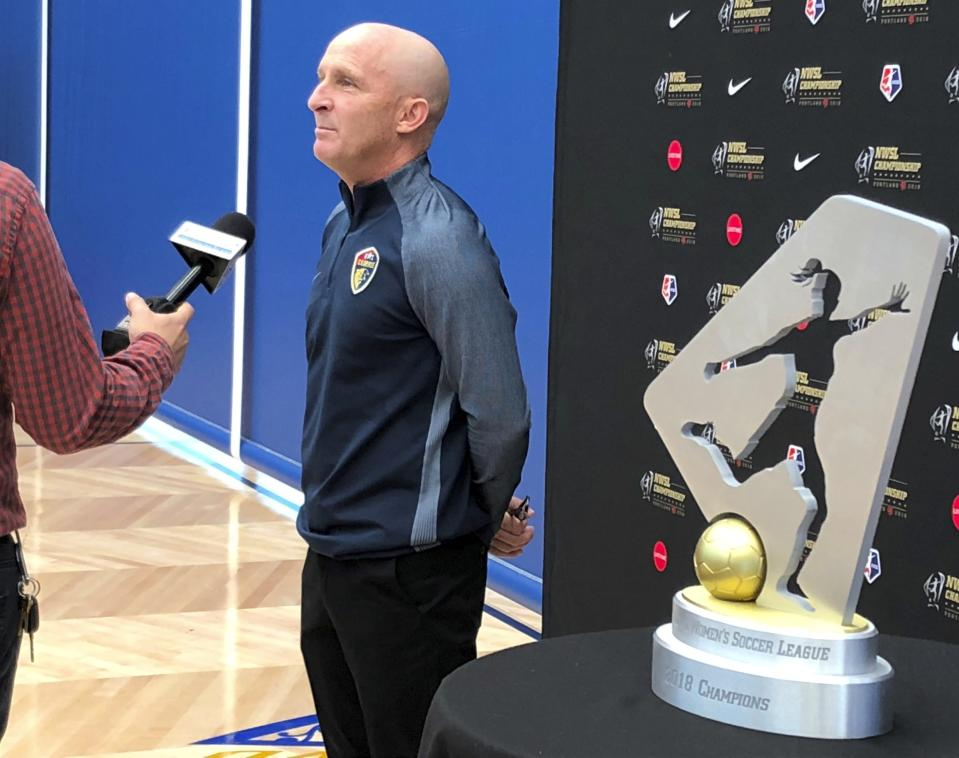 FILE - In this Sept. 20, 2018, file photo, North Carolina Courage coach Paul Riley is interviewed by a reporter next to the trophy for the National Women's Soccer League championship during a media event at Nike in Beaverton, Ore. The National Women's Soccer League will not play the games scheduled for this weekend as it deals with the fallout from allegations of sexual misconduct against a former coach. North Carolina Courage coach Paul Riley was fired by the team following a report in The Athletic that detailed the alleged misconduct, which included claims from two former players of sexual coercion. The NWSL did not specify Friday, Oct. 1, 2021, whether the games were canceled or postponed. (AP Photo/Anne M. Peterson, File)