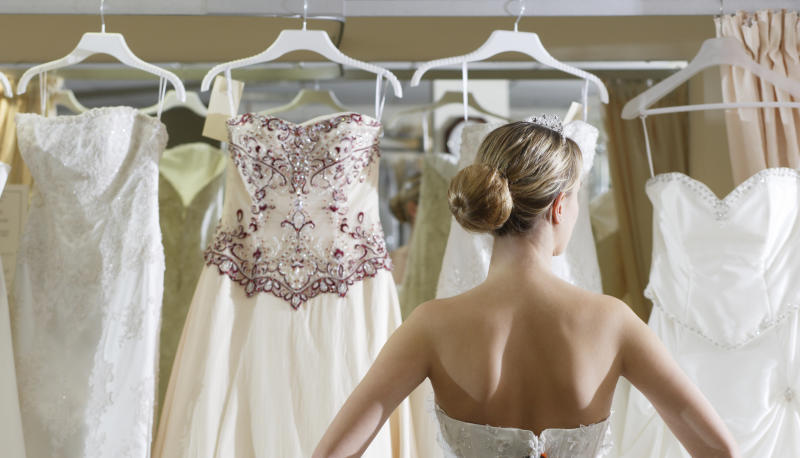 Woman looks at row of wedding gowns don't wear a wedding dress to someone else's wedding