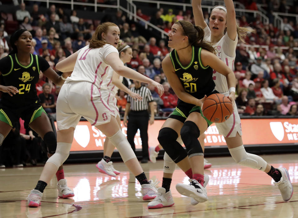 Oregon's Sabrina Ionescu (20) looks to shoot between Stanford's Ashten Prechtel (11) and Lexie Hull, right, in the first half of an NCAA college basketball game Monday, Feb. 24, 2020, in Stanford, Calif. (AP Photo/Ben Margot)