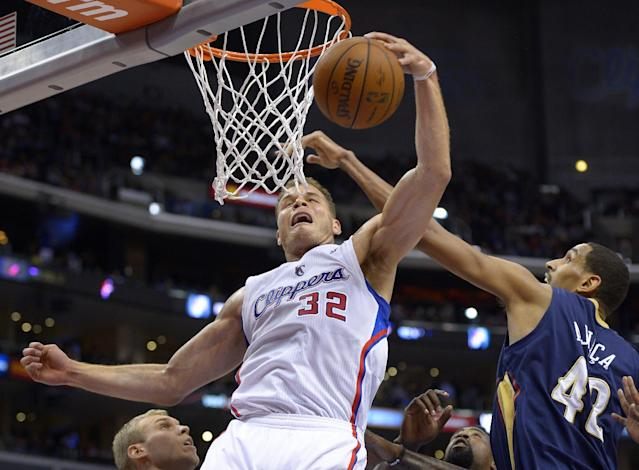 Los Angeles Clippers forward Blake Griffin, left, grabs a rebound away from New Orleans Pelicans center Alexis Ajinca, of France, during the first half of an NBA basketball game, Saturday, March 1, 2014, in Los Angeles. (AP Photo/Mark J. Terrill)