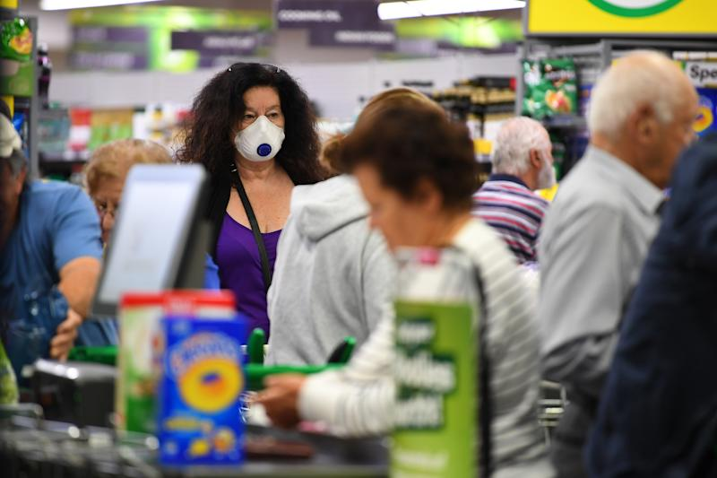 A photo shows a woman wearing a face mask amid a crowd of people inside a Woolworths shopping centre.