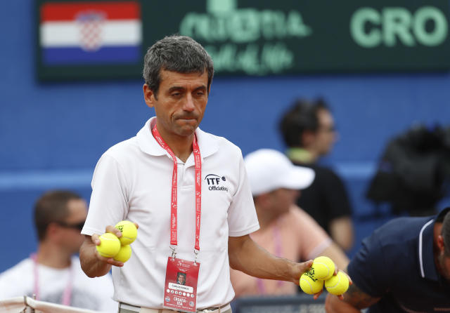 Tennis umpire Carlos Ramos, holds up a set of new tennis balls to be used in the first Davis Cup semifinal singles tennis match between Borna Coric of Croatia and Steve Johson of the United States in Zadar, Croatia, Friday, Sept. 14, 2018. (AP Photo/Darko Bandic)