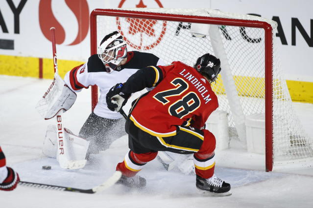New Jersey Devils goalie Mackenzie Blackwood, left, deflects a shot from Calgary Flames' Elias Lindholm during the second period of an NHL hockey game Thursday, Nov. 7, 2019, in Calgary, Alberta. (Jeff McIntosh/The Canadian Press via AP)
