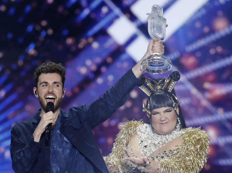 """Duncan Laurence of the Netherlands celebrates with the trophy after winning the 2019 Eurovision Song Contest grand final with the song """"Arcade"""" in Tel Aviv, Israel, Saturday, May 18, 2019. In rear is Israeli Netta Barzilai the winner in 2018. (AP Photo/Sebastian Scheiner)"""
