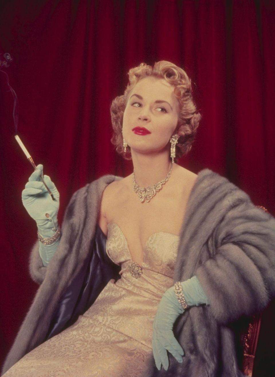 <p>A woman wearing an ornate evening gown with opera gloves and a pelted fur stole. </p>