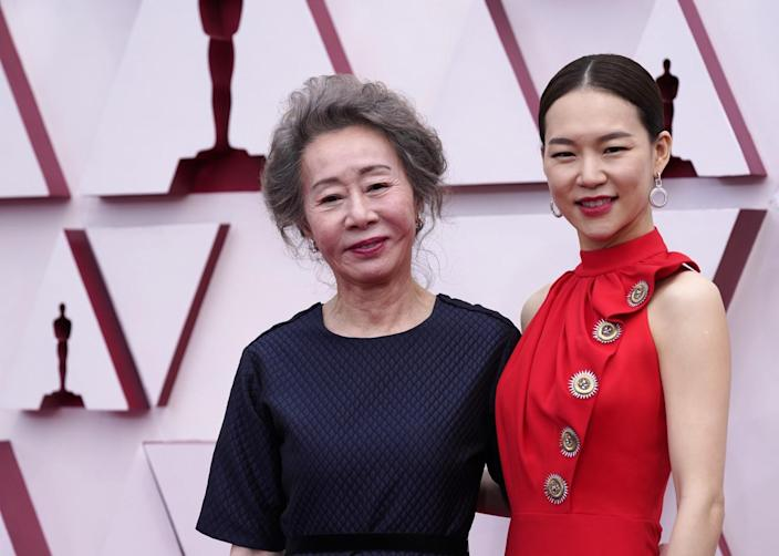 Yuh-Jung Youn wears a dark dress, and Han Ye-ri wears a high-neck red dress with large buttons