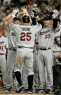 Jim Thome (C) is congratulated by Twins teammates after hitting his 600th home run on August 15, 2011