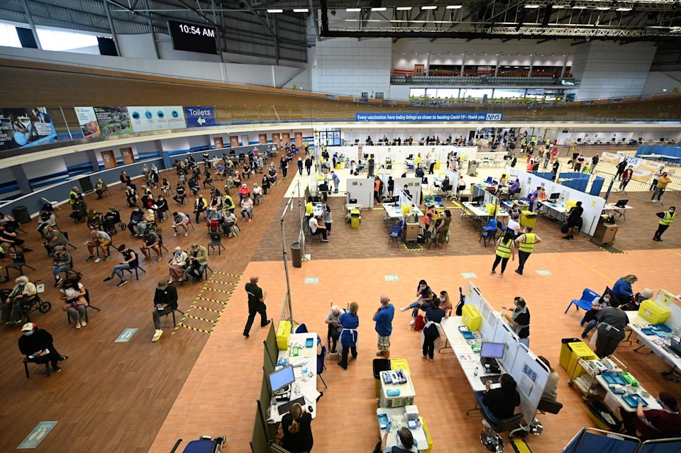 A general view shows various activities as people receive a dose of the BioNTech/Pfizer covid-19 vaccine at a vaccination clinic set up inside the Derby Arena at Pride Park in Derby, Derbyshire on March 31, 2021. - On March 28, 2021, Britain passed the milestone of giving the first vaccine dose to more than 30 million adults, and the government plans to allow outdoor drinking in pub gardens and non-essential retail such as hairdressers in England from April 12. (Photo by Oli SCARFF / AFP) (Photo by OLI SCARFF/AFP via Getty Images)