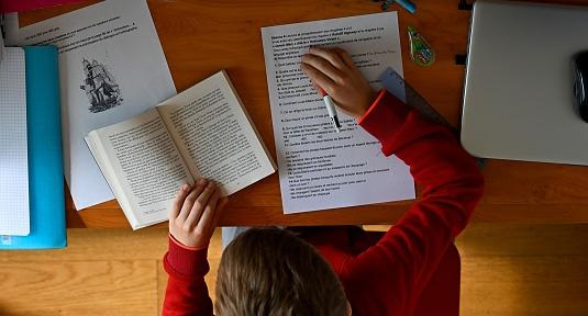 A schoolboy does his homework in his room in Rennes, western France.