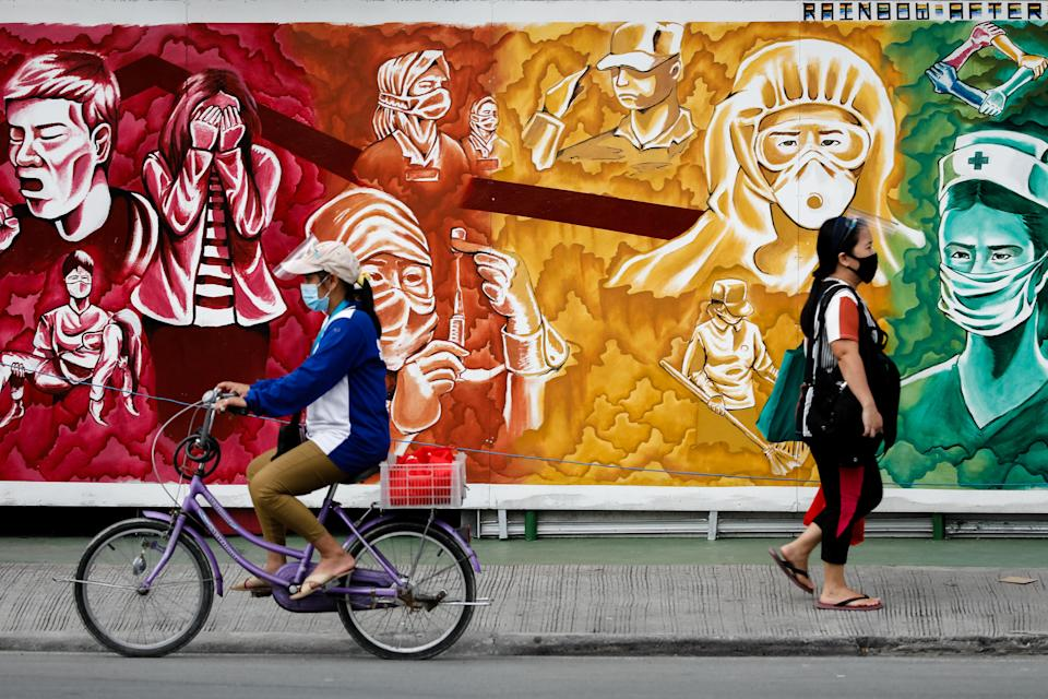FILE PHOTO: People wearing masks for protection against the coronavirus disease (COVID-19) pass a mural dedicated to healthcare workers, in Pasig City, Metro Manila, Philippines, October 30, 2020. (Source: REUTERS/Eloisa Lopez)