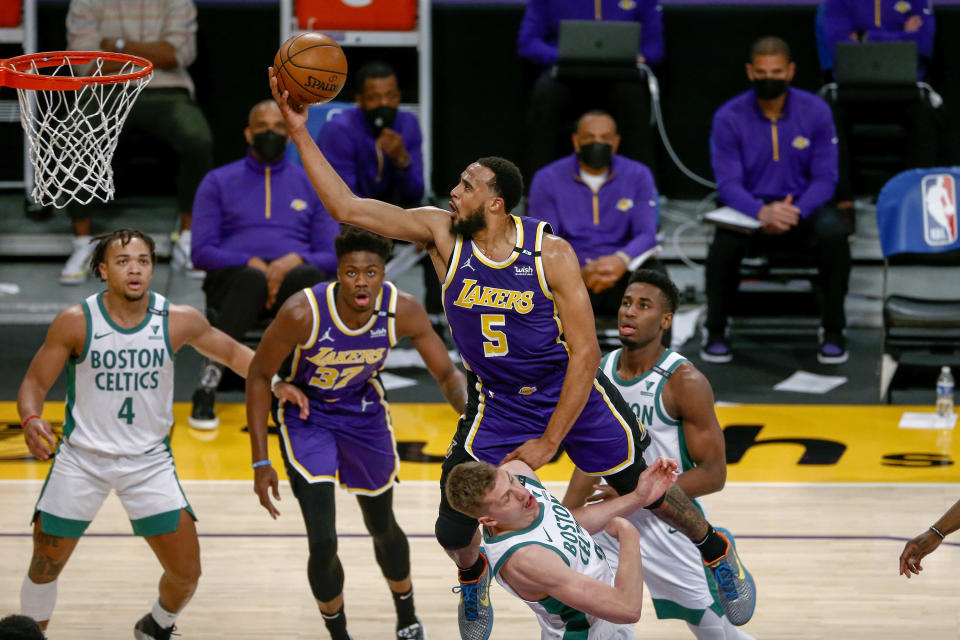 Los Angeles Lakers' Talen Horton-Tucker (5) goes to basket over Boston Celtics' Moritz Wagner (20) during the second half of an NBA basketball game Thursday, April 15, 2021, in Los Angeles. (AP Photo/Ringo H.W. Chiu)