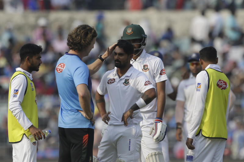 Bangladesh's team physio talks with Liton Das after he was injured by a delivery from India's Mohammed Shami during the first day of the second test match between India and Bangladesh, in Kolkata, India, Friday, Nov. 22, 2019. (AP Photo/Bikas Das)