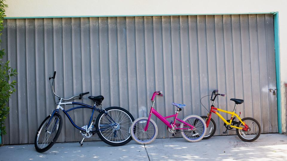 Bicycle, Childhood, Color Image, Day, Door, Driveway, Fun, Garage Door, Horizontal, Motion, Nobody, Outdoors, Photography, Speed, Three Objects, Togetherness, absence, leaning