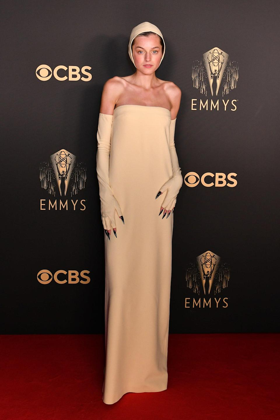 """<em>The Crown</em> actor Emma Corrin wore what they deemed """"Crucible Realness"""" to the awards show celebration in London, donning a custom pale cream strapless Miu Miu gown with matching gloves and a swim-style cap. Emma added a touch of edge and drama with stiletto nails in shiny black."""